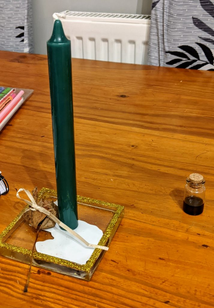 Green candle with a leaf package tied in gold ribbon next to the candle and a small glass bottle of oil near by